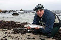 有冬天海鳟的钓鱼者 库存图片