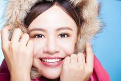 有冬天穿戴毛线衣的微笑的亚裔女孩 隔绝在蓝色bac 免版税图库摄影