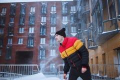 有冬天衣裳的大力士享用雪,寒冷,降雪,飞雪 都市围场背景 免版税库存图片