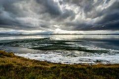有冰川的Winter风景结冰的湖和在集成电路的多云天空 免版税图库摄影