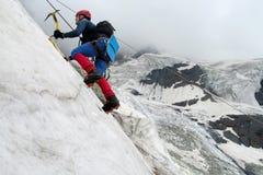 有冰斧的登山人 库存照片