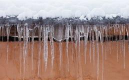 有冰柱的积雪的屋顶 恶劣天气,冬天季节概念,软的焦点,浅深度领域 免版税库存图片