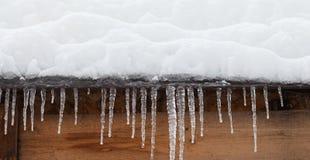 有冰柱的积雪的屋顶 恶劣天气,冬天季节概念,软的焦点,浅深度领域 库存照片