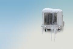 有冰柱的冻空调器在蓝色白色背景 复制空间 免版税图库摄影
