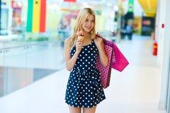 有冰淇凌和购物袋的青少年的女孩 免版税库存图片
