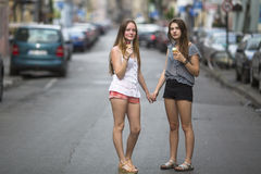 有冰淇凌的两个青少年的女孩在握手的街道上站立 走 免版税库存图片