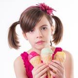 有冰淇凌的小逗人喜爱的女孩在白色 库存图片