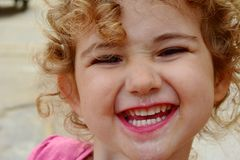 有冰淇凌的幼儿在她的面孔和乐趣表示 免版税库存照片