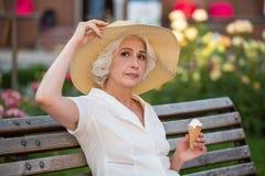 有冰淇凌的成熟夫人 免版税库存照片