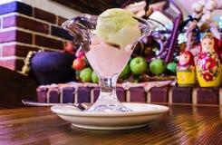 有冰淇凌的美丽的花瓶在水果和蔬菜玩偶和篮子背景的一张木桌上  库存图片