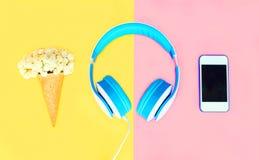 有冰淇凌的耳机开花在五颜六色的黄色桃红色的白色智能手机 库存照片
