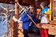 有冰球的年轻人滑冰和棍子在冬天村庄 库存图片