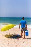 有冰酒吧致冷机的年轻人在海滩ne的太阳伞下 库存图片