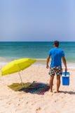 有冰酒吧致冷机的年轻人在海滩ne的太阳伞下 库存照片
