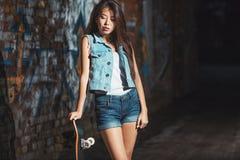 有冰鞋板的,都市生活方式青少年的女孩 免版税图库摄影