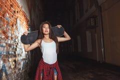 有冰鞋板的,都市生活方式青少年的女孩 免版税库存图片