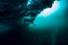 有冲浪板下潜水中的冲浪者与下面大波浪 免版税库存图片