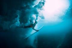 有冲浪板下潜的冲浪者妇女水下与下面大波浪 库存图片