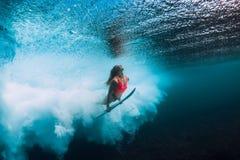 有冲浪板下潜的冲浪者妇女水下与下面海浪 免版税图库摄影