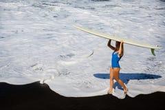 有冲浪板步行的少妇在黑沙子海滩 免版税库存照片