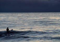 有冲浪板的一位冲浪者在海洋在被月光照亮夜 免版税图库摄影