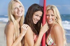 有冲浪板的三位美丽的女子冲浪者 免版税库存图片