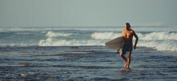 有冲浪板的冲浪者在松巴哇岛,印度尼西亚海岸线  免版税图库摄影