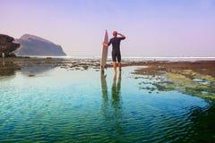 有冲浪板的冲浪者在海岸线 免版税库存照片