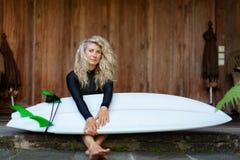 有冲浪板的女孩坐游廊步海滩别墅 免版税库存照片