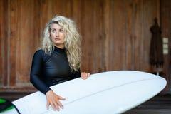 有冲浪板的女孩坐游廊步海滩别墅 库存图片