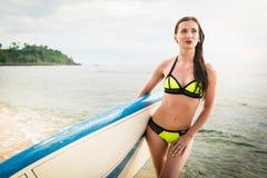 有冲浪板的妇女在她的在热带海洋的胳膊下 免版税库存照片