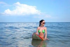 有冲浪板的深色的女孩 库存照片