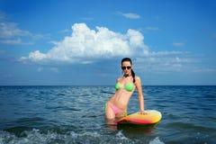 有冲浪板的深色的女孩 免版税库存图片