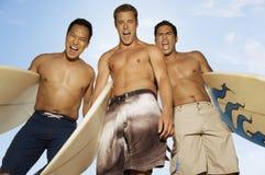 有冲浪板的激动的男性朋友 免版税库存照片