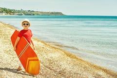 有冲浪板的男孩在海边 免版税库存照片
