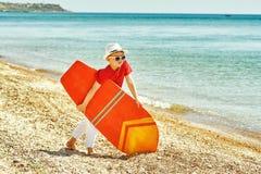 有冲浪板的男孩在海边 库存图片