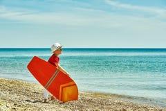 有冲浪板的男孩在海边 库存照片