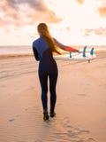 有冲浪板的美丽的少妇冲浪者女孩努力去做海滩的海洋在日落或日出 库存图片