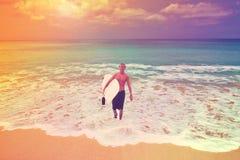 有冲浪者委员会的年轻冲浪者来自后面海洋, Bal 免版税库存照片