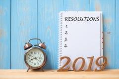有决议文本的2019新年快乐在笔记本、减速火箭的闹钟和木数字在桌和拷贝空间上 库存照片