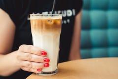 有冷的拿铁的女性行家在现代咖啡馆 背景中断咖啡新月形面包杯子甜点 与冰的咖啡拿铁 与红色修指甲的妇女钉子 女性修指甲 免版税库存照片
