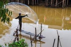 有净钓鱼的渔夫在湄公河三角洲 库存照片