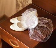 有净面纱和婚礼鞋子的白色帽子 库存照片