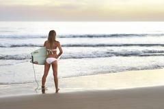 有准备好的委员会的可爱的冲浪者女孩早晨海浪 库存图片