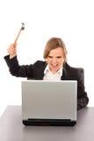 有准备好的锤子的恼怒的女实业家捣毁她的膝上型计算机whil 库存照片