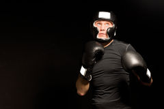 有准备好他的拳头的坚定的年轻拳击手 图库摄影