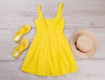 有凉鞋和帽子的黄色礼服 免版税库存图片