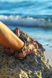 有凉鞋的妇女腿在石近的热带蓝色海菲律宾 免版税库存图片