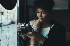 有减速火箭的影片photocamera的两种人种的妇女在咖啡馆 免版税库存照片