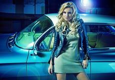 有减速火箭的汽车的白肤金发的端庄的妇女在背景中 图库摄影